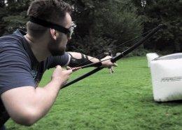 Mann mit sportlicher Schutzbrille spannt einen Bogen und zielt. Auf einer Wiese stehen Deckungen. Im Hintergrind sind Gegenspieler sichtbar