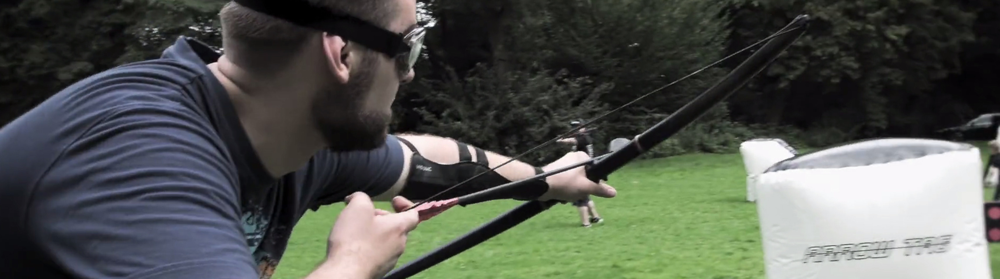 Junger Mann im T-Shirt mit sportlicher Schutzbrille spannt einen Bogen mit einem Pfeil und zielt. Im Hintergrund steht eine Deckung mit der Aufschrift Arrow Tag.