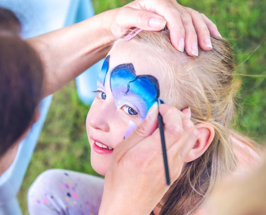 Nahaufnahme eines Gesichts von einem kleinen Mädchen, das gerade mit einem Pinsel geschminkt wird. Dabei entsteht letztendlich ein blauer Schmetterling.