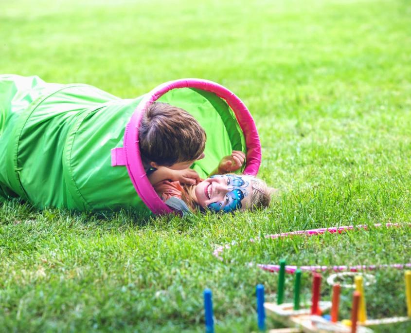 Zwei geschminkte Kinder toben in einer Rolle auf einer Wiese weswegen Sie laut lachen. Ebenfalls auf der Wiese liegen ein Hulahoop-Reifen und ein Wurfspiel.