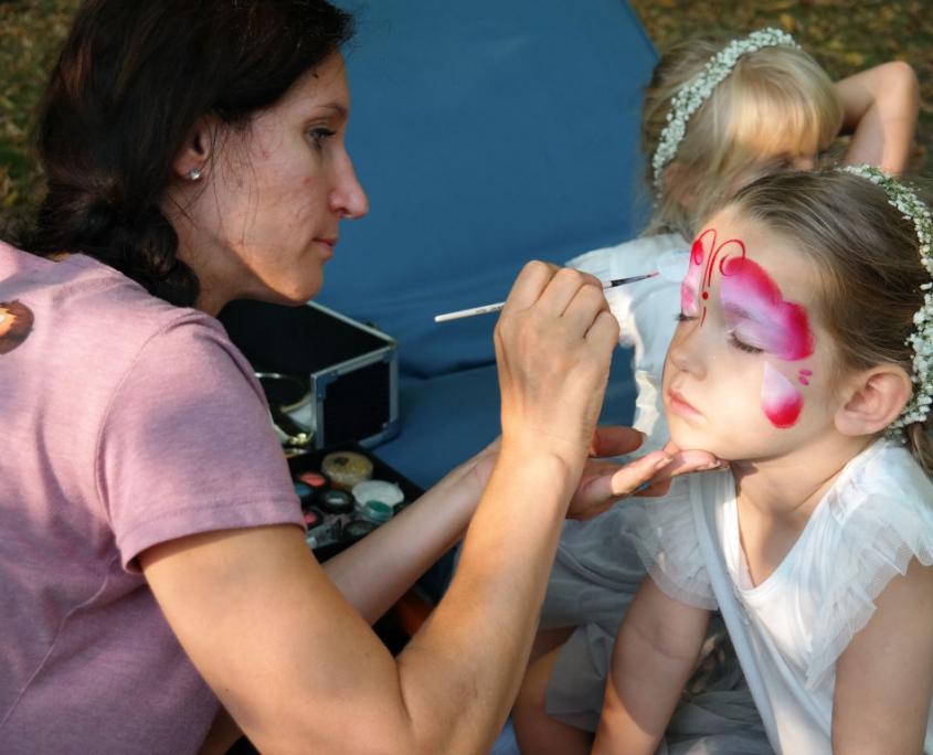 """Eine junge, sympathische Frau im lilafarbenen """"creativkopf""""-T-Shirt bemalt konzentriert mit einem Pinsel ein kleines Mädchen. Es wird schließlich ein rosa-roter Schmetterling entstehen. Das Mädchen im weißen Kleid trägt einen geflochtenen Blumenkranz im Haar."""