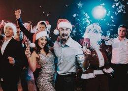 Konzept Weihnachtsfeier, Junge Businessleute tanzen. Gläser mit Sekt in der Hand. Festlich angezogen. Weihnachtsfeier mit Pfiff.