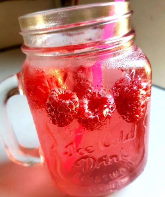 Ein Glas selbstgemachte Himbeerlimonade. Modernes Henkelglas mit Limo, frischen Himbeeren und einem Strohhalm.