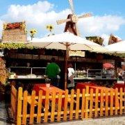 Marktstand mit süßen Backwaren. Liebevoll dekoriert mit Sonnenblumen und Weinranken. Vor dem Imbiss ist ein Biergarten aufgebaut, der zum Verweilen einlädt. Die Gäste sind beim Genießen der Speisen und Getränke durch helle Schirme von der starken Herbstsonne geschützt. Die Große Mühle auf dem Dach lässt die Gäste das Mühlenstübchen schnell finden.