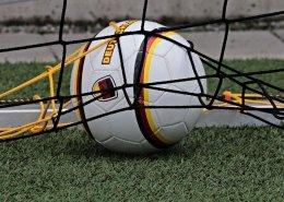 Ein weißer Fußball mit schwarz-rot-gelben Umrandungen liegt in einem Tornetz.