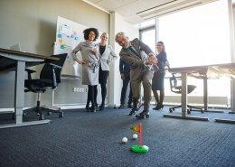 In einem Büro mit blauem Fußboden ist eine Zielfanhe für Minigolfbälle. ein Ball liegt vor dem Loch. Ein Spieler schlägt gerade einen zweiten Ball in die Richtung. seine Teammitglieder freuen sich und feuern ihn an. Alle sind in Businesskleidung. Büromöbel sowie ein Flipchart sind am Rand des Büros.