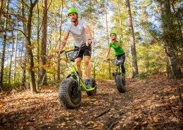 Monsterroller sind große Tretroller mit extra breiten Reifen mit starkem Profil. 2 Personen sind beim Downhill im Wald. Der Man in sportlicher Kleidung fähr bzw. rollt vorweg. Die Frau hinterer. Beide sind fröhlich und begeistert.