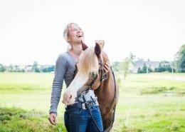 Psychologin Anja Heine schmust lachend mit ihrem Pferd auf einer Weide.