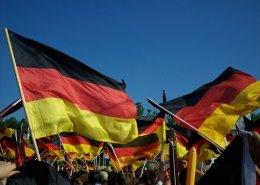 Große Personengruppe beim Public Viewing. Viele Deutschlandfahnen werden geschwungen. Fröhliche Menschen jubeln und feiern.