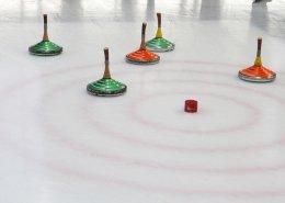 Beim Eisstockschießen liegt die Gaube im Mittelkreis. Eines der drei grünen Eisstöcke liegt am dichtesten am Ziel. Zwei orangene Stöcke kurz dahinter. Im Hintergrund sieht man die Füße der Spieler.