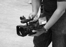 """Schwarzweiß Foto eines Kameramannes, der seine Videokamera auf hüfthöhe hält und über den kleinen Kameramonitor etwas verfolgt. um den Hals hängt ein Schlüsselband mit der Karte """"All Access""""."""