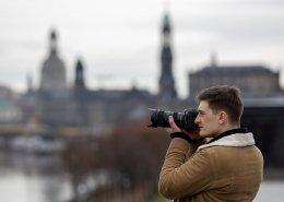 Der Workshopleiter im Fokus mit seiner Spiegelreflexkamera fotografiert in die Ferne. Im Hintergrund verschwommen die Skyline von Dresden.