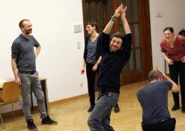 Eine gruppe befindet sich in einem großen leeren Raum mit Parkettfußboden. Im Team werden übungen zum Schauspielen durchgeführt. Fünf Teammitglieder mit unterschiedlichsten demografischen Eigenschaften haben gemeinsam Spaß an dem Workshop.