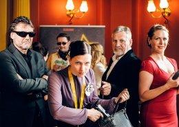 """Wieder posieren der Darsteller der Krimmi Dinner Truppe. Eine Frau zieht eine Pistole aus der schwarzen Handtasche. Eine Dame im roten Kleid lächelt. Die Männer haben einen sehr """"coolen Blick"""" drauf."""