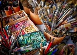 Ein sehr harmonisches, farbenfrohes Bild. Auf einem Tisch stehen diverse Dosen mit Pinseln, Stifte, Farben und Kreide. Es zeigt vorbereitende Maßnahmen für ein Puzzle Painting Event.