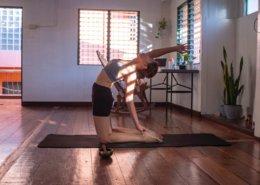 Junge, athletische Frau macht eine Yoga Übung auf einer Fitnessmatte auf einem Holzfußboden. Im Hintergrund ein Schreibtisch mit einem Computer.