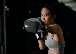 Junge Frau mit einem leichten asiatischen Taint mit Boxhandschuhen beim Training. Dunkler Hintergrund.